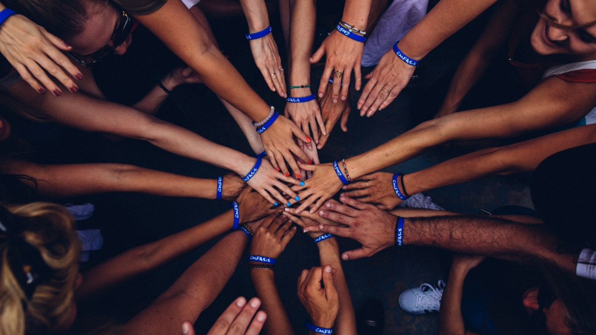 Several hands placed on top of each other to signify team spirit
